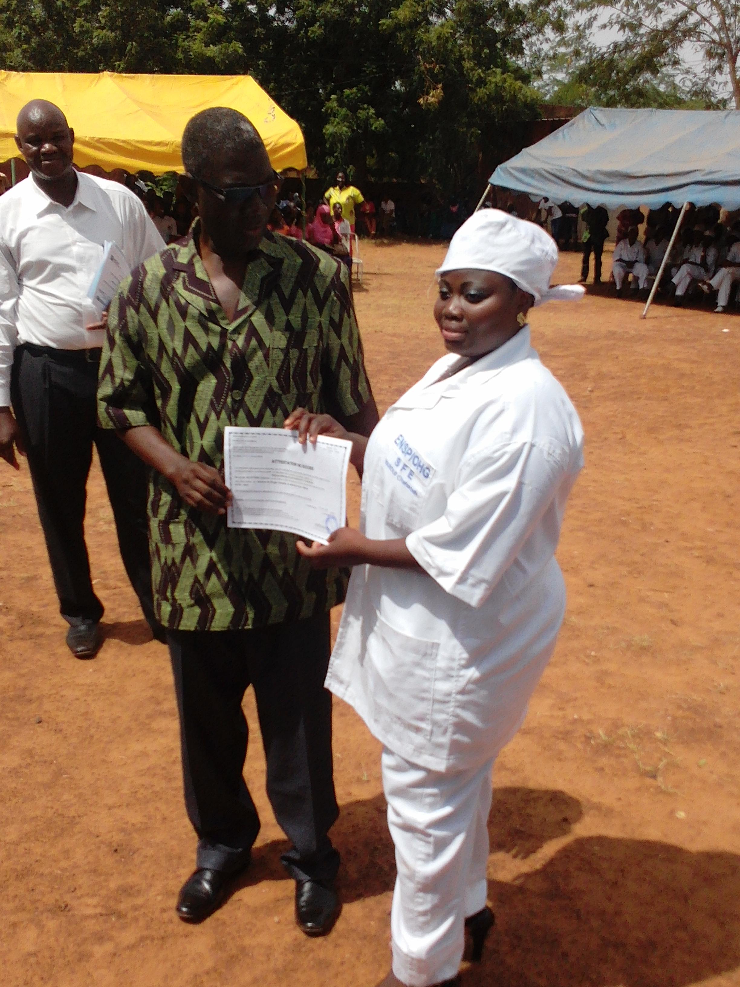 Le gouverneur remettant une                               attestation au major des sages femmes, de nationalité béninoise.