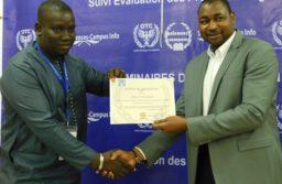 Un nouveau spécialiste recevant son certificat de spécialisation en suivi-évaluation des projets et programmes de la main du coordonnateur de OTC